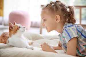 photo of Cute little girl with cat at home